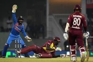 West Indies batsman Carlos Brathwaite (C) falls as Indian wicketkeeper Dinesh Karthik (L) reacts with West Indies batsman Denesh Ramdin (R) looking on during the second T20 cricket