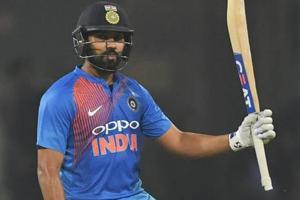 Indian cricket captain Rohit Sharma raises his bat after scoring a half century (50 runs) during the second T20 cricket match between India and West Indies at the Bharat Ratna Atal Bihari Vajpayee Ekana Cricket Stadium in Lucknow.