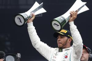 SAO PAULO: Mercedes driver Lewis Hamilton, of Britain, raises trophies after winning the Brazilian Formula One Grand Prix at the Interlagos race track in Sao Paulo.