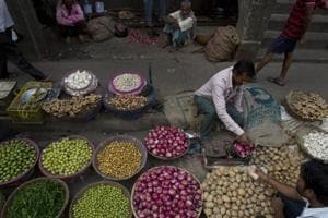 A street vendor sells vegetables in a wholesale market in Guwahati.