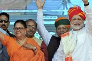 Prime Minister Narendra Modi and Rajasthan chief minister Vasundhara Raje greet their supporters during