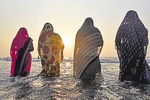 Devotees offer prayers to the Sun god after taking bath on occasion of Chhath Puja, at Juhu Chowpatty on Tuesday.