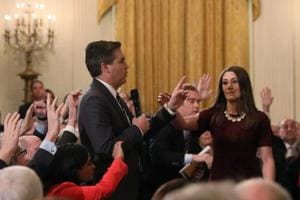 A White House intern reaches for and tries to take away the microphone held by CNN correspondent Jim Acosta as he questions US President Donald Trump during a news conference at the White House in Washington, US on  November 7.