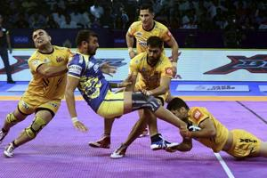 Telugu Titans (Yellow) players in action against Puneri Paltan during their Pro Kabaddi league  2018.