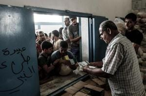 Palestinians receive aids at a United Nations food distribution centre in  refugee camp.