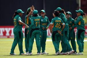 Pakistan players celebrate the fall of an Ireland wicket.