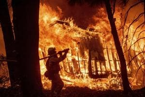 Firefighter Jose Corona sprays water as flames consume from the Camp Fire consume a home in Magalia, Calif, November 9, 2018. (AP Photo/Noah Berger, File)