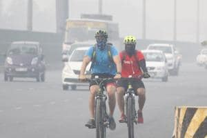 Cyclists with covered faces ride in heavy smog & air pollution at Gurugram - Delhi Expressway, Saturday, November 10, 2018.