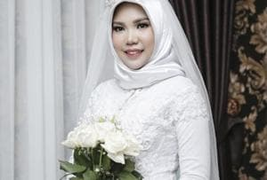 In this photo taken on Sunday, Nov. 11, 2018, and released by Intan Syari, Indonesian Intan Syari poses in her wedding dress with a bouquet of flowers on the day of her planned wedding in Pangkal Pinang, Indonesia. Syari who was engaged to a man who died on a Lion Air flight that plunged into the sea has worn her wedding dress on the day they were to have been married.