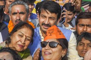 BJP activists take a selfie with Delhi BJP chief Manoj Tiwari during a campaign in Dehradun on Wednesday.