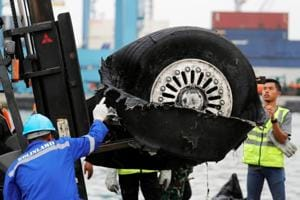 A worker assists his colleague during the lift up of a damaged tyre from Indonesian forensic policemen stand beside a damaged tyre from the the Lion Air flight JT610 jet.