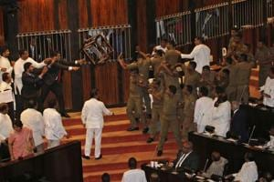 Lawmakers supporting disputed Prime Minister Rajapksa throw a chair towards police officers escorting the speaker inside parliament in Colombo, Sri Lanka, Friday, Nov. 16, 2018.