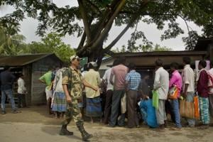 A paramilitary person walks past as people whose names were left out in the National Register of Citizens (NRC) draft stand in a queue to collect forms to file appeals near a NRC center on the outskirts of Guwahati on August 13.