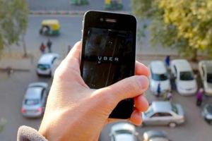 The Uber smartphone app, used to book taxis using its service, is pictured over a parking lot.