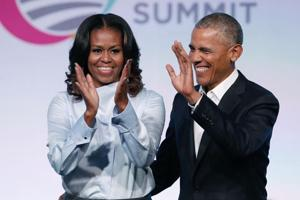 In this file photo taken on October 31, 2017, former US President Barack Obama and first lady Michelle Obama arrive at the Obama Foundation Summit in Chicago, Illinois.