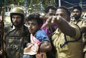 Police personnel detain the devotees who were staging