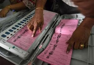 A polling staff tallies the candidates' names on the Electronic Voting Machines (EVM) before leaving for their respective booths
