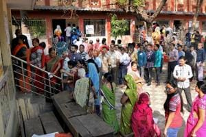 Voters stand in a queue at a polling station to cast their votes for the 2nd phase of Assembly elections, in Raipur on November 20.