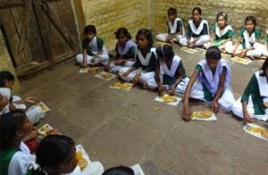 Students of Government Middle School at Parsouriya village in Sagar eating their mid-day meal on pieces of papers.