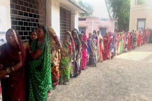 Women stand in a queue to cast their votes at a polling booth during the Assembly Election, in Banahil on November 20.