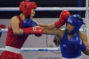 Mary Kom of India (in blue) and Kim Hyang Mi of North Korea (in red) compete during their 45-48 kg category semi-final fight.