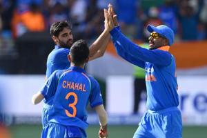 Bhuvneshwar Kumar celebrates with teammates after picking a wicket during a match.