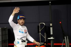 McLaren driver Fernando Alonso waves to spectators in the pit during the qualifying session at the Yas Marina racetrack in Abu Dhabi.
