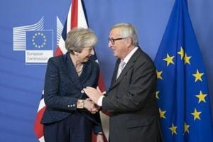Theresa May, U.K. prime minister, left, reacts as she shakes hands with Jean-Claude Juncker, president of the European Commission, during a meeting ahead of Brexit negotiations in the Berlaymont building in Brussels, Belgium.