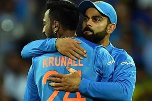 Virat Kohli (R) greets spin bowler Kurnal Pandya for his wicket off Australia