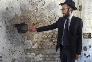 Chabad House Mumbai director Rabbi Israel Kozlovsky gestures at bullet marks from the 26/11 attacks.