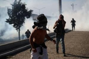 A migrant with his face covered runs from tear gas released by U.S border patrol near the fence between Mexico and the United States in Tijuana, Mexico.