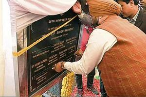 Punjab minister SS Randhawa covers Congress leaders' names with black tape to avoid sharing space with Akalis on the foundation stone of the Kartarpur corridor project in Gurdaspur on Monday.