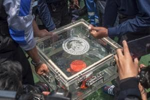 Members of the National Transportation Safety Committee lift a box containing the flight data recorder from a crashed Lion Air jet onboard a rescue ship anchored in the waters of Tanjung Karawang, Indonesia.