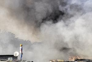 A man watches as smoke billows from the Patil Estate slums in Shivajinagar on Wednesday. Twenty fire brigade vehicles and 20 water tankers were used to control the fire. There are 1,176 shanties in Patil Estate area.