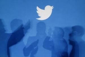 The shadows of people holding mobile phones are cast onto a backdrop projected with the Twitter logo.