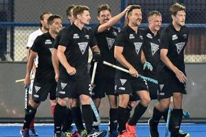 New Zealand (black) player Kane Russell celebrates with teammates after scoring a goal in a match against France (white) for Men