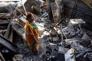 A woman looks onto the burnt remains of her home in Patil estate after the fire was dosed down.