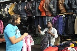 Mohammad Shariq, a deaf and mute cloth trader, interacts with a customer.