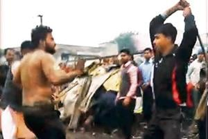 A screenshot of the video n shows a mob beating up a man with sticks in outer Delhi's Kirari. Another screenshot (left) shows a policeman, standing as a mute spectator, in the background.