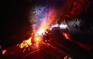 In a photograph dated January 29, 2013, miners keep warm by a fire inside a deep mine shaft near Rymbai village in Meghalaya.