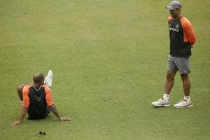 Indian cricketer M S Dhoni, right, and Shikhar Dhawan talk during a practice session.