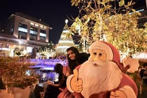 People take photographs infront of a Christmas tree at a mall in New Delhi.