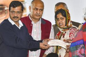 Delhi Chief Minister Arvind Kejriwal (L) hands over a cheque to the family members of martyred Delhi Traffic Police constable Beenesh Kumar, in New Delhi, Friday, Nov. 30, 2018.