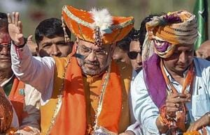 BJP President Amit Shah waves at supporters at an election roadshow .
