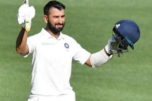 Cheteshwar Pujara celebrates after scoring his century during day one of the first Test match between Australia and India.