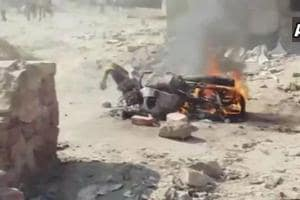A motorcycle burning after a violent clash between workers of two different parties at a polling booth in Rajasthan's Fatehpur town during voting for the assembly elections (ANI/Twitter)
