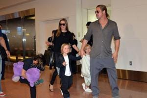 Brad Pitt (R) and Angelina Jolie (C), accompanied by their children, arrived at Haneda International Airport in Tokyo.