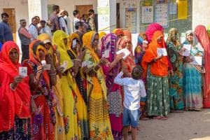 Voters show their identity cards as they wait in queues at a polling station to cast their votes for state Assembly elections in Jaipur on Friday.