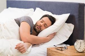 Man sleeping with alarm clock in foreground.