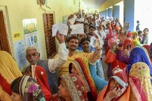 Assembly elections 2018: Voters show their identity cards as they wait in queues at a polling station to cast their votes for state Assembly elections, in Jaipur, Friday.